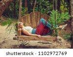 tourist woman relaxing on a... | Shutterstock . vector #1102972769