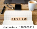 Small photo of Closeup on notebook over wood table background, focus on wooden blocks with letters making Review text. Concept image. Laptop, glasses, pen and mobile phone in defocused background
