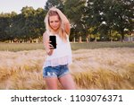 a beautiful girl at sunrise in... | Shutterstock . vector #1103076371