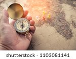 Small photo of Tourists hold a compass and locate a place on a world map.