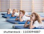 boy relaxing on a blue mat with ... | Shutterstock . vector #1103094887