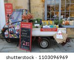 Small photo of Broadway, Gloucestershire, England, UK. 15 May 2018. A Piaggio Ape 50 three wheeled commercial vehicle loaded with fresh produce outside a shop.