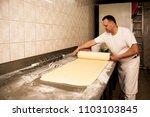 man baker working in bakery shop | Shutterstock . vector #1103103845