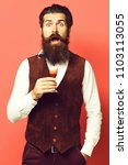 Small photo of handsome bearded man with long beard and mustache on surprised face holding glass of alcoholic shot in vintage suede leather waistcoat on red studio background