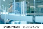 Small photo of Busy International Office, Beautiful Caucasian Woman Shows Documents to a Black Colleague while Walking Through Glass Hallway. In the Background Diverse Group of Creative Colleagues Working.