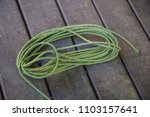 green rope rolled up on wood... | Shutterstock . vector #1103157641
