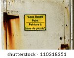 Small photo of Bi-lingual sign warning of lead based paint on an old rusty door