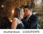 Small photo of Wedding. Bride in a green dress. A large wedding bouquet. The first meeting is just married. He and she are smiling. Loft style. Brick wall. Romantic dinner. Fireplace. Greens in the interior.