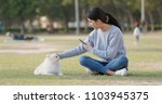 woman taking photo with her dog    Shutterstock . vector #1103945375