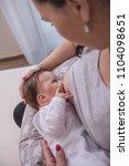 mother breastfeeding baby on... | Shutterstock . vector #1104098651