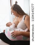 mother breastfeeding baby girl... | Shutterstock . vector #1104145277
