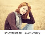 Beautiful red-haired girl at yellow autumn grass. - stock photo