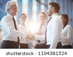 young and mature businessmen... | Shutterstock . vector #1104381524