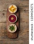hummus snacks on a wooden board ... | Shutterstock . vector #1104424271