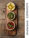 hummus snacks on a wooden board ... | Shutterstock . vector #1104424274