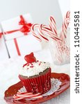 Chocolate cupcake with vanilla frosting, decorated with a edible ornament and pearls. - stock photo