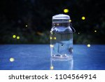 Stock photo fireflies in a jar outdoors at night 1104564914