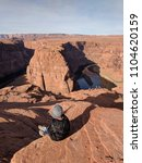 Small photo of A boy sitting on top of a rock overlooking the beautiful landscapes of Horseshoe Bend in Page, Arizona.