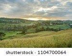 rice field on hill with sunset... | Shutterstock . vector #1104700064