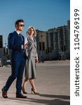 Small photo of young stylish business people with car alarm remote walking on parking