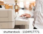 Small photo of A man using a copier in the office.