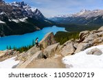 A woman hiking on the rock with Magnificent view of blue water at Peyto Lake of Banff National Park in Canada