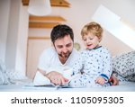 father with toddler boy reading ... | Shutterstock . vector #1105095305