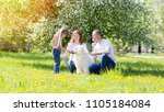 happy family with a white dog... | Shutterstock . vector #1105184084