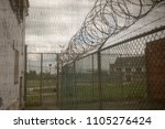exercise yard with razor wire... | Shutterstock . vector #1105276424