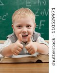 Cheerful smiling child at the blackboard. School concept - stock photo