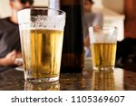 a glass full of beer and foam.... | Shutterstock . vector #1105369607