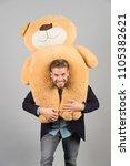 man carries giant teddy bear on ... | Shutterstock . vector #1105382621