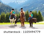 kids riding pony in the alps... | Shutterstock . vector #1105494779