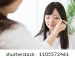 attractive asian woman making up | Shutterstock . vector #1105572461