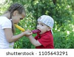 pretty little girl feeding a... | Shutterstock . vector #1105643291