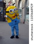 "Small photo of SAINT-PETERSBURG, RUSSIA - JUNE 3, 2018 - Person in costume of character of cartoon ""Minions"" distributes flyers on the street of St-Petersburg"