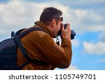 a man with a camera in his hands | Shutterstock . vector #1105749701