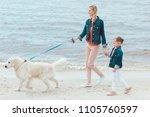 Stock photo beautiful family walking with golden retriever dog on sea shore 1105760597