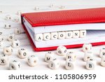 Small photo of Word Account written in wooden blocks in red notebook on white wooden table. Wooden abc.