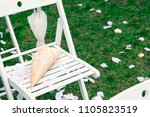 Stock photo rose petals on the white chair on wedding close up copy space toned 1105823519