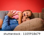 Small photo of Cute little girl adoring her mother, hugging while laying on couch
