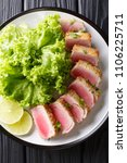 Small photo of Delicious steak ahi tuna in bread crumbs panko with lettuce and lime closeup on a plate on a black table. Vertical top view from above