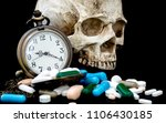 Small photo of Antique clock on multicolored of drug and capsule behind clock is a skull. is on the black background. Close up. We are against drugs (anti drugs), cure in container for health.