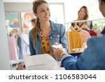 woman in clothing store paying... | Shutterstock . vector #1106583044