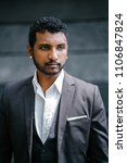 Small photo of Head shot portrait of a young Indian man in a 3-piece suit and pocket square. He is sporting a beard and diamond earrings which makes him roguish and cool.