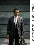 Small photo of A confident and cool Indian Asian man in a 3 piece suit is holding an exercise bag and standing against a grey wall in the day. He is wearing sunglasses and diamond earrings which makes him roguish.