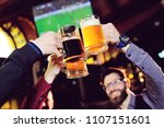 Stock photo a group of young men s friends in a bar or pub drinking beer with glasses and watching football 1107151601