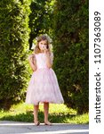 Small photo of A girl in a pink lavish dress smells a flower in the park on the Sunset.