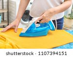 woman ironing clothes on board... | Shutterstock . vector #1107394151