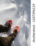 Small photo of Reckless hiker with orange snowshoes and velvet pants on the edge of a crevasse in the glacier in the mountains